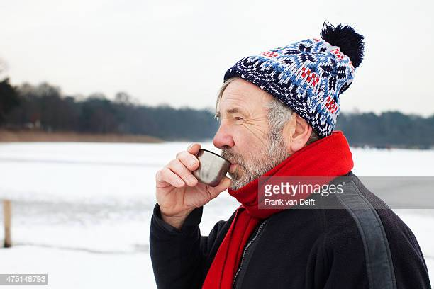 Man outdoors having hot drink