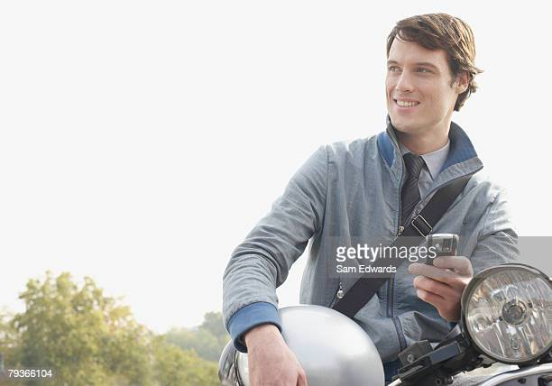 Homme à l'extérieur s'appuyant sur un scooter tenant son téléphone mobile