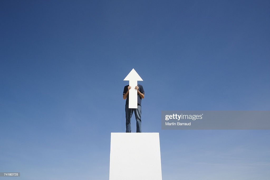 Man outdoors on wall with blank arrow : Stock Photo