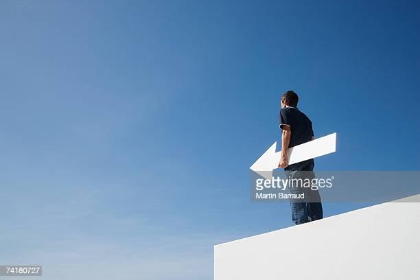 Uomo all'aperto vuota sulla parete con freccia