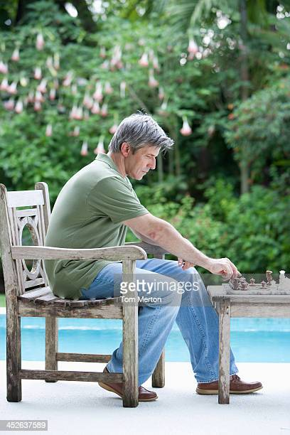 Man outdoors playing chess by swimming pool