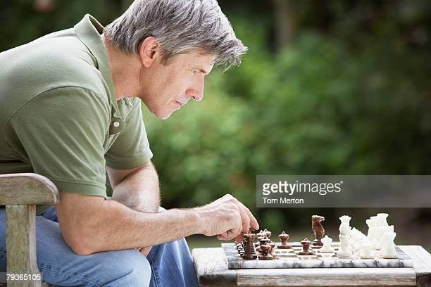 man outdoors playing chess - chess stock pictures, royalty-free photos & images