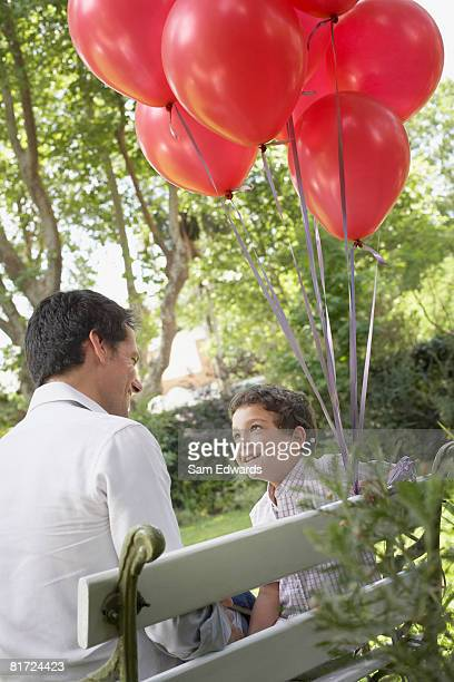 Man outdoors sitting on bench with young boy beside him holding red balloons smiling