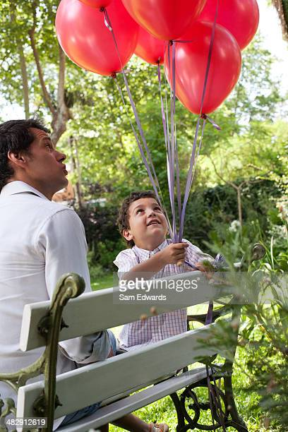 Man outdoors sitting on bench with young boy