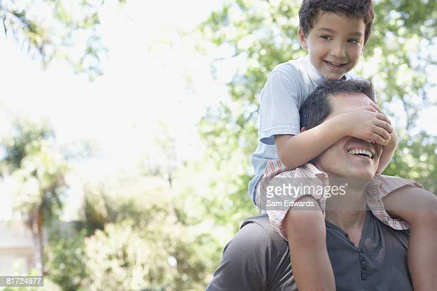 Man outdoors with young boy on shoulders covering his eyes smiling