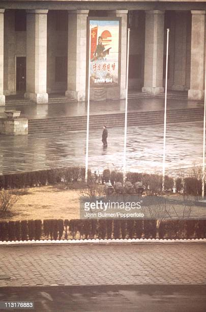 A man outside a government building on which a poster depicting North Korean revolutionary forces is displayed North Korea February 1973