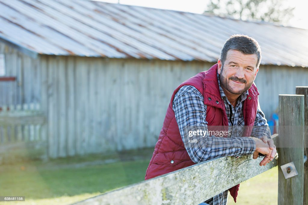 Man outside barn leaning on wooden fence : Stock Photo