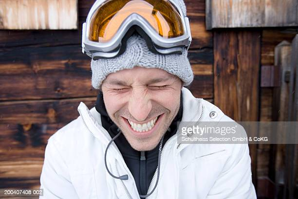 Man outside chalet wearing ski goggles on head, wincing, close-up