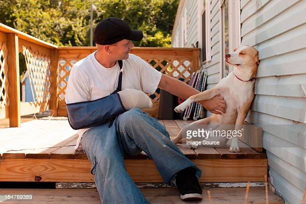 Man outside house with arm in sling and dog