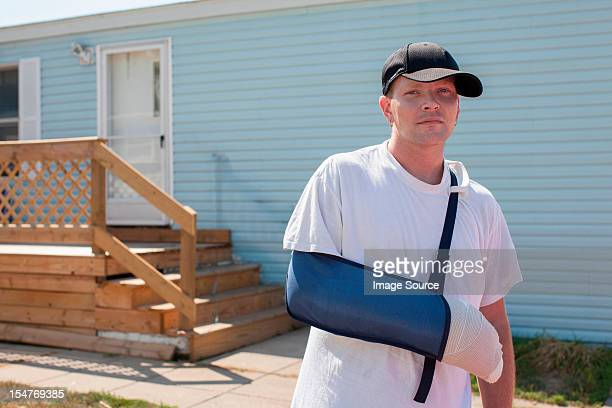 Man outside house with arm in sling