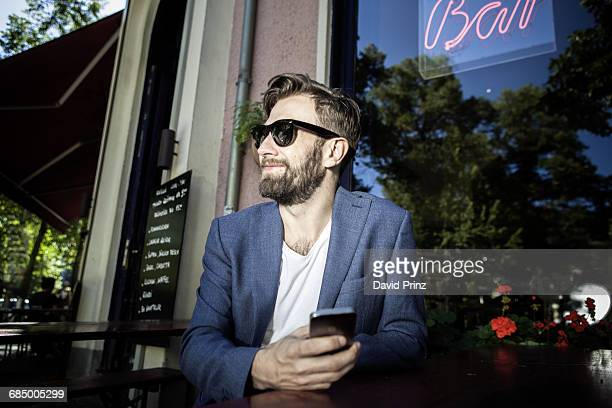 Man outside of bar, holding smartphone smiling, Berlin, Germany