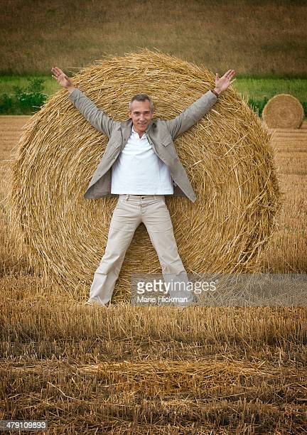 Man outstretched in front of haybale
