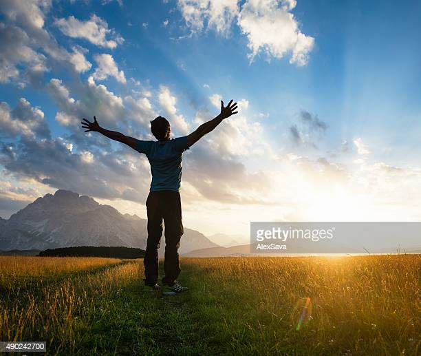 Man outstretching his arms on a sunlit meadow at sunset