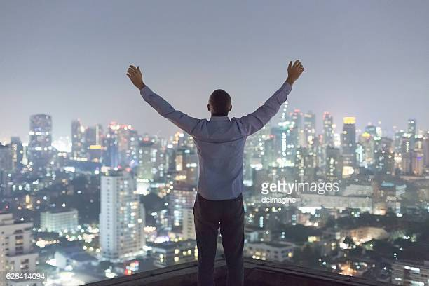 Man over top skyscraper, arms raised
