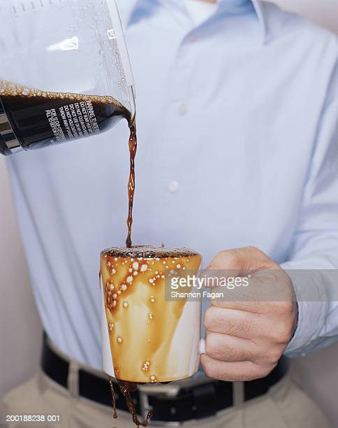 man overfilling mug with black coffee, mid section - overflowing stock pictures, royalty-free photos & images