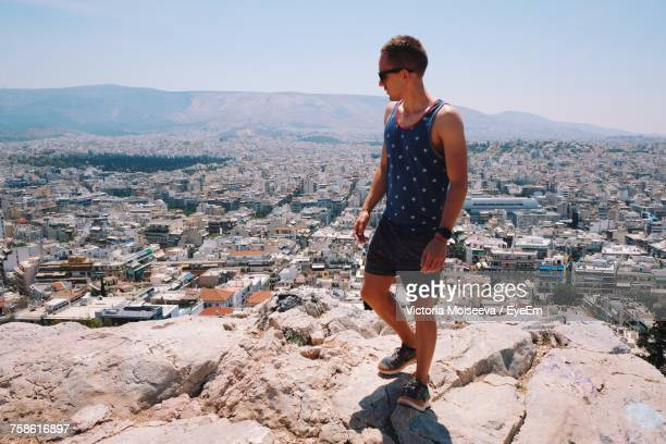 man overlooking cityscape while standing on mountain during sunny day - 見渡す ストックフォトと画像