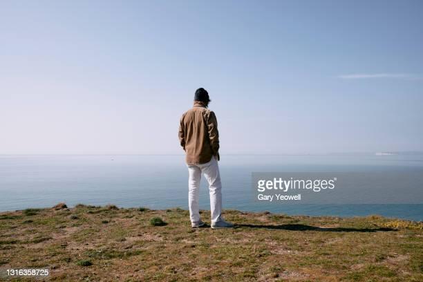 man overlooking dorset coastline - scenics stock pictures, royalty-free photos & images