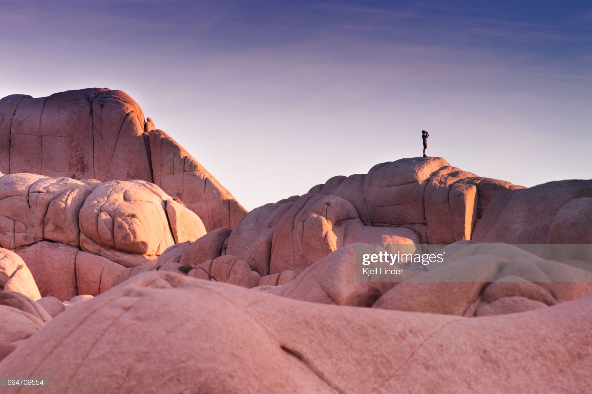 Man overlooks Joshua Tree boulders during sunset : Stock Photo