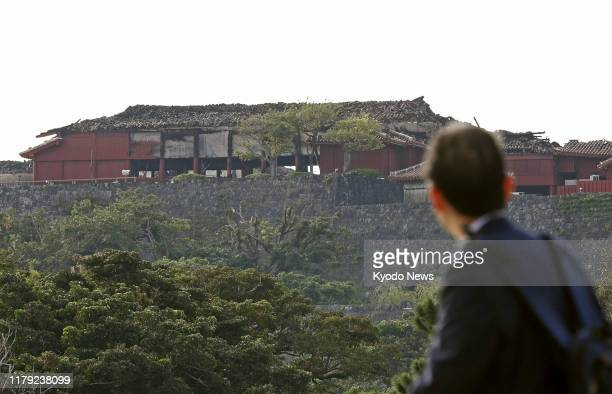 A man overlooks Shuri Castle at a World Heritage site in Naha Okinawa Prefecture southern Japan on Nov 1 2019 The castle was razed by fire the...