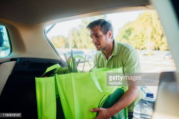man packing bags with groceries into the car trunk - car trunk stock pictures, royalty-free photos & images