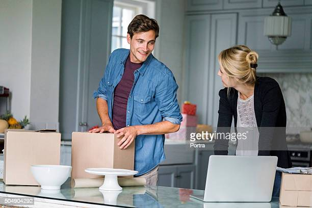 Man packing boxes while talking with woman at home