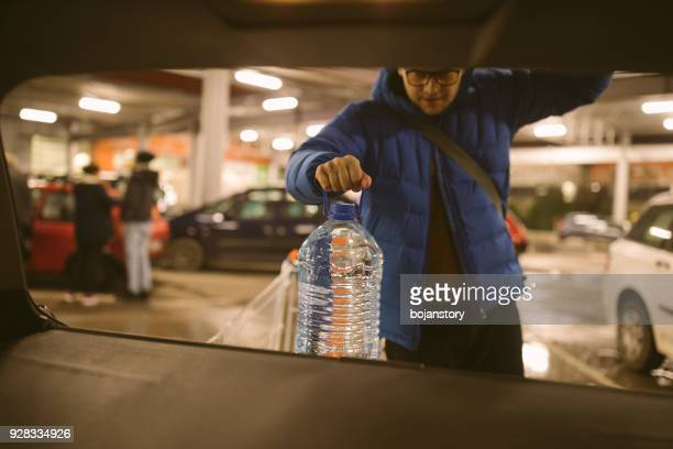 man packing groceries from supermarket in car trunk - carrying imagens e fotografias de stock