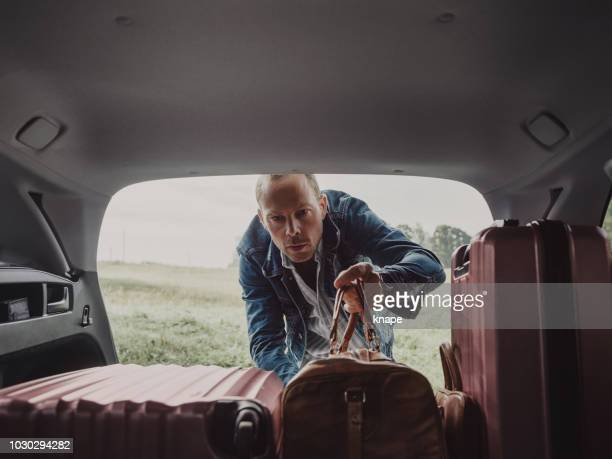 man packing in his luggage suitcase in his car ready for road trip - boot stock pictures, royalty-free photos & images