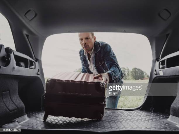man packing in his luggage suitcase in his car ready for road trip - car trunk stock pictures, royalty-free photos & images