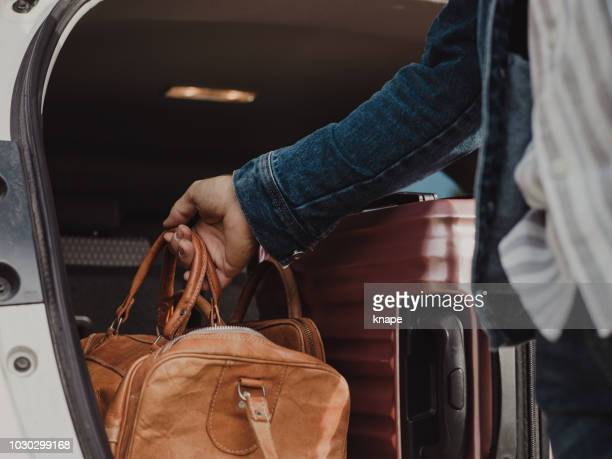 man packing in his luggage suitcase in his car ready for road trip - packing stock pictures, royalty-free photos & images