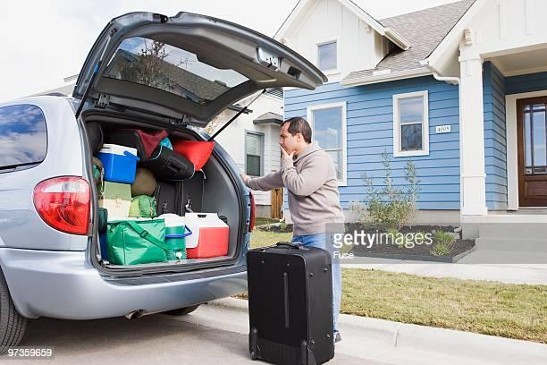Man packing minivan for road trip