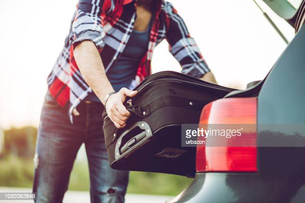 man packing suitcase in a car - putting stock pictures, royalty-free photos & images