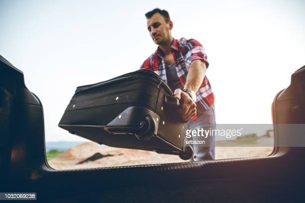 man packing suitcase in a car - car trunk stock pictures, royalty-free photos & images