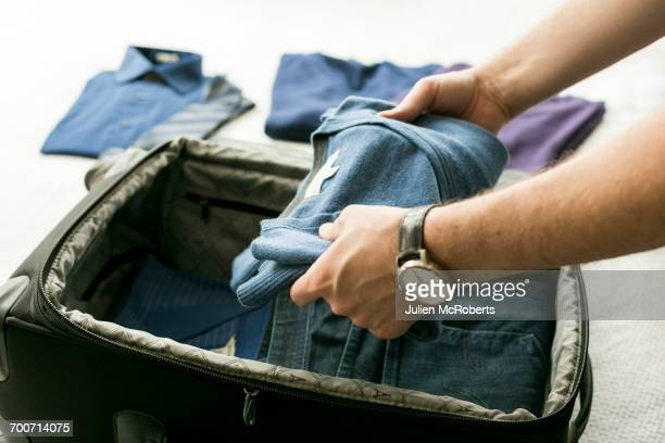 man packing sweater into suitcase - packing stock pictures, royalty-free photos & images