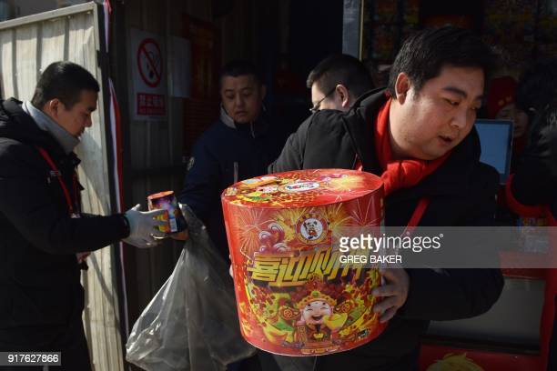 A man packs fireworks for customers at a stall on the outskirts of Beijing in the buildup to Lunar New Year celebrations on February 13 2018 Beijing...