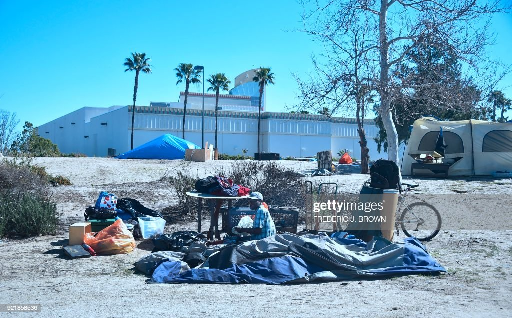 A man packs his belongings at a homeless encampment beside the Santa Ana River on February 20, 2018 in Anaheim, California. Officials in Orange County began moving homeless transients out of the homeless tent encampments to shelters or motels as part of the settlement worked out by homeless advocates and the county under supervision of a federal court judge. / AFP PHOTO / Frederic J. BROWN