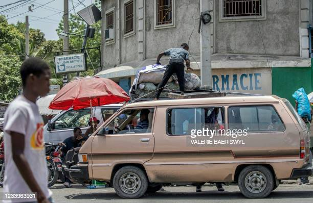 Man packs luggage onto the top of a van at Portail Leogane in Port-au-Prince July 13, 2021 in the wake of Haitian President Jovenel Moise's...