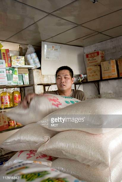 A man packs sacks of rice at a grain wholesalers shop in the town of Longyan in southern China's Fujian Province May 12 2008 A steady dietary...
