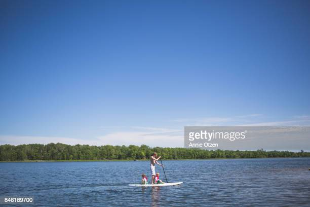 Man Paddle Boarding with Children Riding along