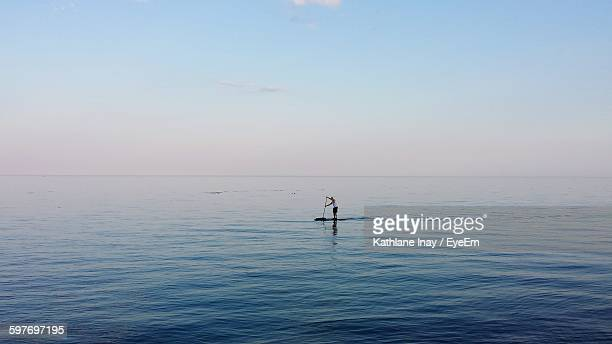 Man Paddleboarding At Sea Against Sky
