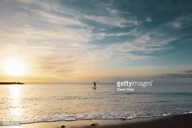 man paddleboarding at sunset in front of mt. fuji - front view ストックフォトと画像
