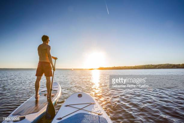 Man Paddleboarding During Sunset