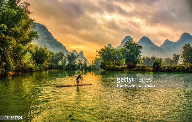 man paddleboarding in lake against mountains during sunset - vietnam fotografías e imágenes de stock