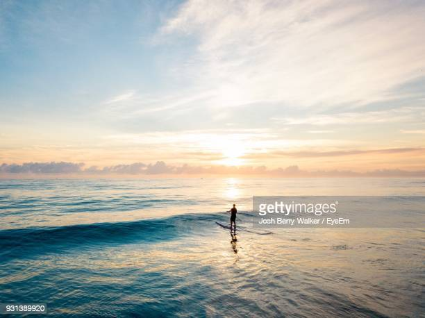 man paddleboarding in river against sky - queensland foto e immagini stock
