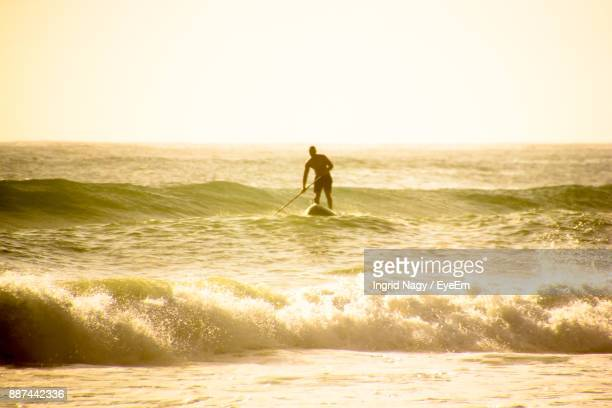 Man Paddleboarding On Sea Against Clear Sky During Sunset