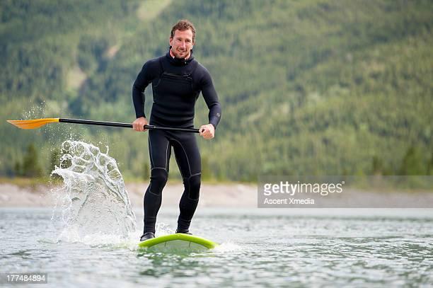 Man paddleboards across mountain lake