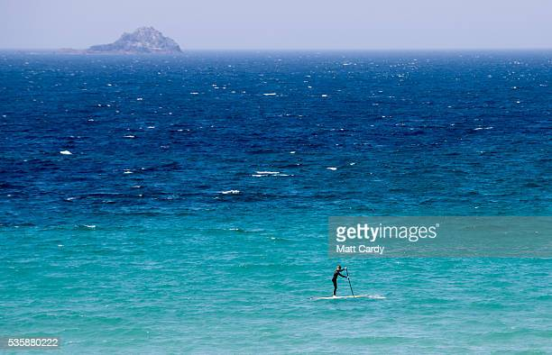 A man paddleboards as people enjoy the fine weather at Sennen Cove on May 30 2016 in Cornwall England As some parts of the UK were bathed in sunshine...