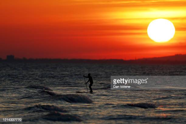 A man paddleboards in the English Channel next to Brighton beach after recent incidents of members of the public ignoring government advice on social...