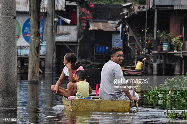 A man paddles a boat to ferry the passengers inside the submerged residential compund at Artex in Malabon City North of Manila on Sunday Today marks...