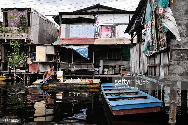 A man paddles a inside the submerged residential compund at Artex in Malabon City North of Manila on Sunday Today marks the celebration of the World...