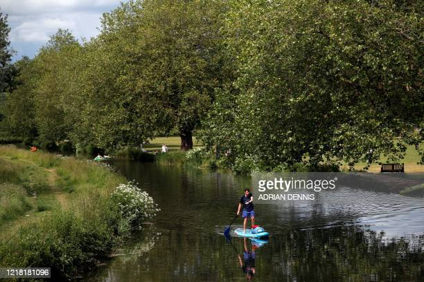Man paddles an SUP along the River Itchen in Winchester, southern England on June 7 as lockdown measures are partially eased during the COVID-19...